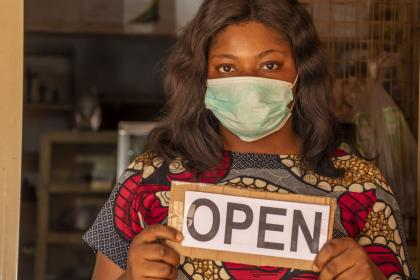 An African female entrepreneur wearing a mask stands in front of her store