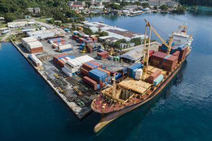 Container ship unloads cargo at dock in Micronesia