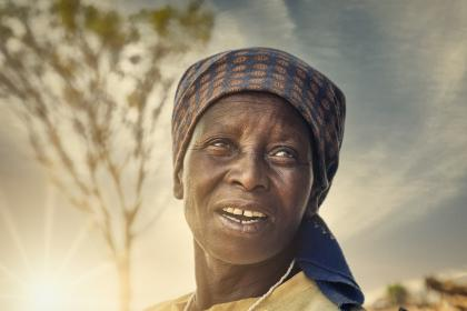 African woman standing in sun-set in front of tree